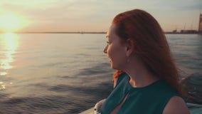 Ragazza felice dei capelli rossi in vestito sull'imbarcazione a motore Bello tramonto intrattenimento stock footage