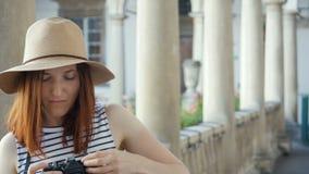 Ragazza felice dei pantaloni a vita bassa che fa foto con la retro macchina fotografica sulla via della città archivi video