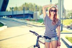 Ragazza felice dei pantaloni a vita bassa con la bici nella città Immagine Stock Libera da Diritti