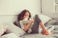Ragazza felice del bambino che gioca con gli orsacchiotti nella sua stanza, sedentesi sul letto Fotografia Stock