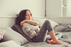 Ragazza felice del bambino che gioca con gli orsacchiotti nella sua stanza, sedentesi sul letto Fotografie Stock
