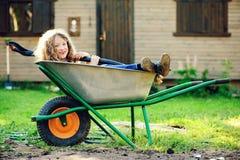 Ragazza felice del bambino che gioca nel giardino di estate con la carriola Immagine Stock