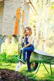 Ragazza felice del bambino che gioca nel giardino di estate con la carriola Fotografia Stock
