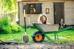 Ragazza felice del bambino che gioca nel giardino di estate con la carriola Immagine Stock Libera da Diritti