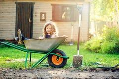 Ragazza felice del bambino che gioca nel giardino di estate con la carriola Fotografie Stock Libere da Diritti
