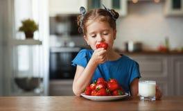 Ragazza felice del bambino che mangia le fragole con latte immagini stock