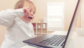 Ragazza felice del bambino che ride mentre per mezzo del suo computer portatile Immagine Stock Libera da Diritti