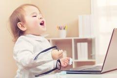 Ragazza felice del bambino che ride mentre per mezzo del suo computer portatile Fotografie Stock Libere da Diritti