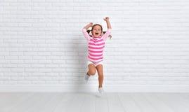 Ragazza felice del bambino che salta intorno alla parete vuota Fotografia Stock Libera da Diritti