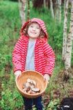 Ragazza felice del bambino con i funghi selvaggi commestibili selvaggi sul piatto di legno Immagine Stock