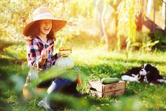 Ragazza felice del bambino con il cane dello spaniel che gioca piccolo agricoltore nel giardino di autunno Immagine Stock Libera da Diritti