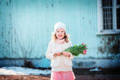 Ragazza felice del bambino con il mazzo dei tulipani divertendosi sulla passeggiata in molla in anticipo Fotografie Stock