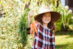 Ragazza felice del bambino dell'agricoltore che seleziona il raccolto domestico fresco della carota di crescita Immagine Stock Libera da Diritti