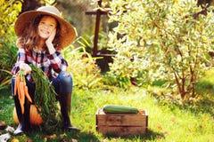 Ragazza felice del bambino dell'agricoltore che si siede con il raccolto di autunno nel giardino Immagine Stock