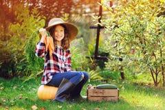ragazza felice del bambino dell'agricoltore con il raccolto di autunno - zucche, carote e zuccini organici Immagini Stock Libere da Diritti