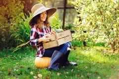 ragazza felice del bambino dell'agricoltore con il raccolto di autunno - zucche, carote e zuccini organici Fotografie Stock