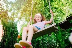 Ragazza felice del bambino su oscillazione, attività sulle vacanze estive Fotografie Stock Libere da Diritti