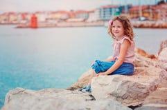 Ragazza felice del bambino sulla spiaggia sulle vacanze estive in Piran, Slovenia, con la vista della città su fondo Fotografie Stock
