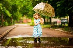 Ragazza felice del bambino in vestito con un ombrello e gli stivali di gomma in pozza immagine stock libera da diritti