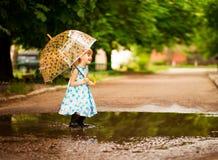 Ragazza felice del bambino in vestito con un ombrello e gli stivali di gomma in pozza sulla passeggiata di estate fotografie stock