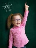 Ragazza felice del bambino in vetri con l'idea luminosa Fotografie Stock Libere da Diritti