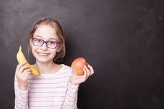 Ragazza felice del chid con la mela e la banana alla lavagna Fotografia Stock