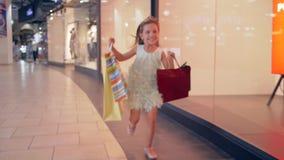 Ragazza felice del cliente con i sacchi di carta nella fretta per ottenere sconto in boutique video d archivio