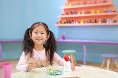 Ragazza felice del piccolo bambino divertendosi da dipingere sulla bambola dello stucco dell'interno immagine stock