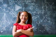 Ragazza felice del ritratto che risolve problema per la matematica complesso sulla lavagna Immagini Stock