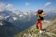 Ragazza felice del viaggiatore con zaino e sacco a pelo in montagne Fotografia Stock