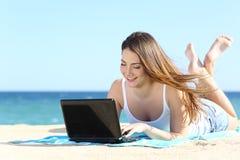 Ragazza felice dell'adolescente che passa in rassegna media sociali in un computer portatile sulla spiaggia Immagine Stock