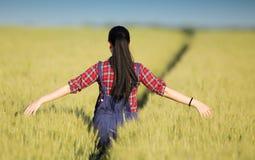 Ragazza felice dell'agricoltore nel giacimento di grano Immagini Stock