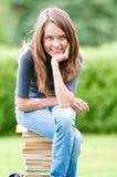 Ragazza felice dell'allievo che si siede sui libri Fotografia Stock