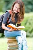Ragazza felice dell'allievo che si siede sul mucchio dei libri Immagine Stock