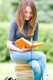 Ragazza felice dell'allievo che si siede sul mucchio dei libri Fotografia Stock