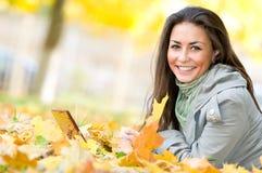 Ragazza felice dell'allievo che si trova in autunno Fotografia Stock