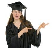 Ragazza felice dell'allievo di graduazione che indica obliquamente Immagini Stock Libere da Diritti