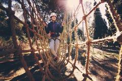 Ragazza felice della scuola che gode dell'attività in un parco rampicante di avventura fotografia stock libera da diritti