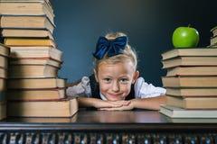 Ragazza felice della scuola che si siede vicino alla tavola con molti libri Immagine Stock Libera da Diritti
