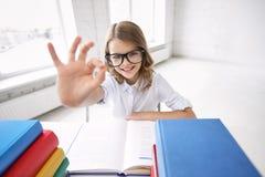 Ragazza felice della scuola con i libri che mostrano segno giusto Immagini Stock