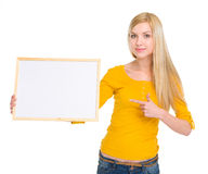 Ragazza felice dello studente che indica sul bordo in bianco Fotografia Stock