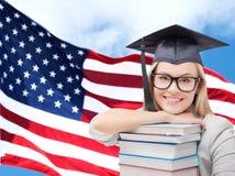 Ragazza felice dello studente con i libri sopra la bandiera americana Fotografia Stock