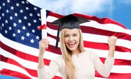 Ragazza felice dello studente con il diploma sopra la bandiera americana Fotografia Stock