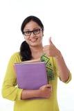 Ragazza felice dello studente con il pollice su contro bianco Fotografie Stock Libere da Diritti