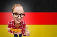 Ragazza felice dello studente con le cartelle che mostrano i pollici su Immagine Stock