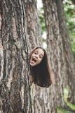 Ragazza felice dietro l'albero immagini stock libere da diritti