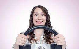 Ragazza felice divertente di emozioni con il volante dell'automobile, concetto automatico fotografie stock