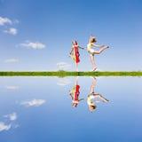 Ragazza felice due che salta insieme sul prato verde Fotografie Stock