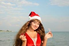 Ragazza felice e bella Santa Claus sulla spiaggia Fotografie Stock Libere da Diritti