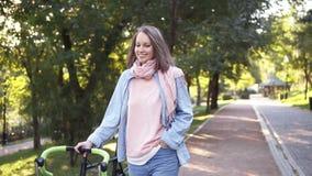 Ragazza felice e sorridente che cammina oltre ad un parco della bicicletta di mattina La donna che cammina con la sua bici di tre archivi video